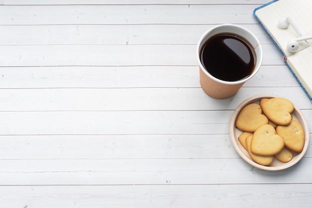 Czarna kawa w papierowej filiżance i ciasteczka w kształcie serc na białym tle. płaskie miejsce do kopiowania, widok z góry.