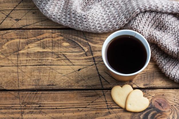 Czarna kawa w papierowym kubku i ciasteczka w kształcie serc