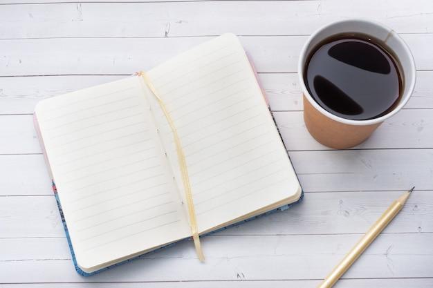 Czarna kawa w papierowym kubku i notatniku