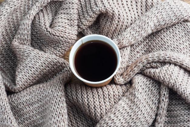 Czarna kawa w papierowym kubku na ciepłym kocu. leżał płasko