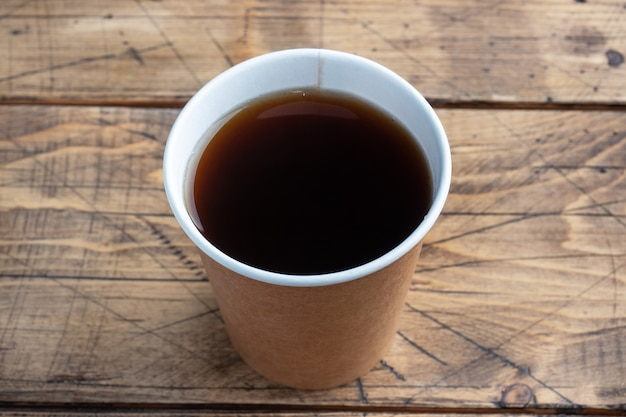 Czarna kawa w papierowym kubku na drewnianym tle. płaskie miejsce do kopiowania, widok z góry.