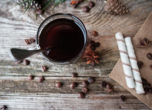 Czarna kawa w szklanej filiżance na drewnianym stole z sosnowych gałęzi, ziaren kawy, gwiazd anyżu, cynamonu i bułek waflowych