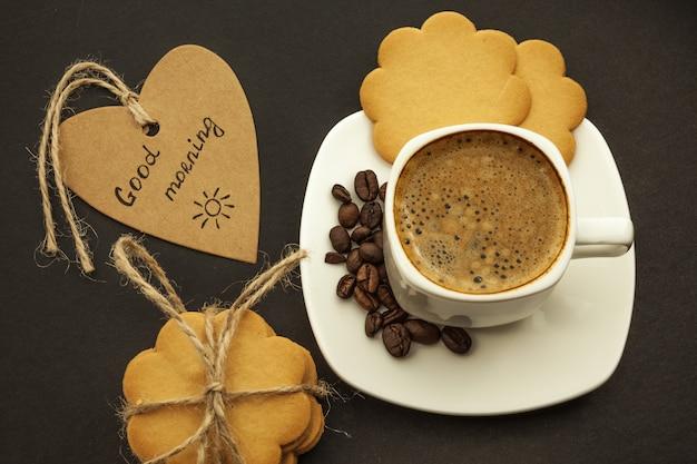 Czarna kawa z kawowymi fasolami i ciastkami na ciemnym tle. śniadanie, widok z góry.