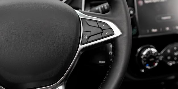 Czarna kierownica z wielofunkcyjnymi przyciskami do szybkiego sterowania, zbliżenie w samochodzie.