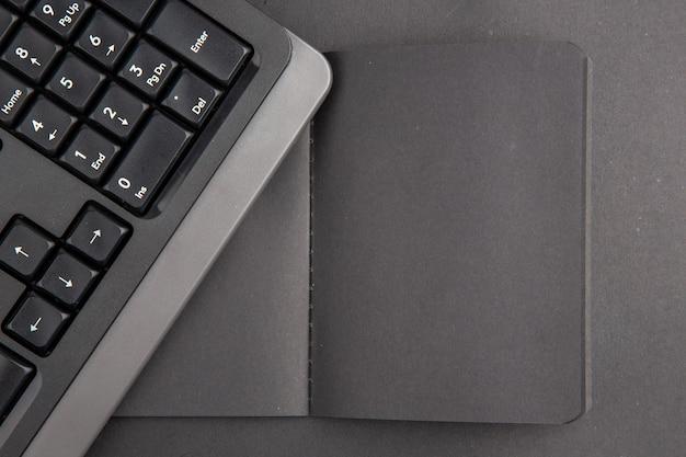 Czarna klawiatura notebooka z widokiem z góry na ciemnym stole