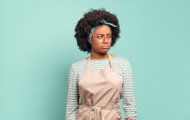 Czarna kobieta afro czuje się smutna, zdenerwowana lub zła i patrzy w bok z negatywnym nastawieniem