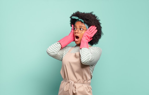 Czarna kobieta afro czuje się szczęśliwa, podekscytowana i zaskoczona, patrząc w bok z obiema rękami na twarzy. koncepcja sprzątania... koncepcja gospodarstwa domowego