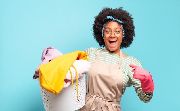 Czarna kobieta afro czuje się szczęśliwa, zaskoczona i dumna, wskazując na siebie z podekscytowanym, zdumionym spojrzeniem. koncepcja sprzątania... koncepcja gospodarstwa domowego