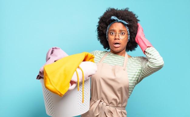 Czarna kobieta afro czuje się zestresowana, zmartwiona, niespokojna lub przestraszona, z rękami na głowie, panikująca z powodu błędu. koncepcja sprzątania... koncepcja gospodarstwa domowego