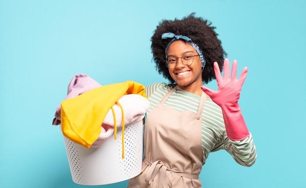 Czarna kobieta afro uśmiechnięta i patrząca przyjaźnie, pokazująca numer pięć lub piąty z ręką do przodu, odliczając w dół. koncepcja sprzątania... koncepcja gospodarstwa domowego