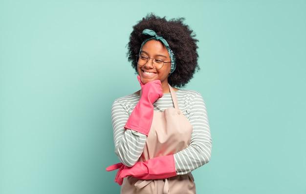 Czarna kobieta afro uśmiechnięta ze szczęśliwym, pewnym siebie wyrazem twarzy z ręką na brodzie, zastanawiająca się i patrząca w bok. koncepcja sprzątania... koncepcja gospodarstwa domowego