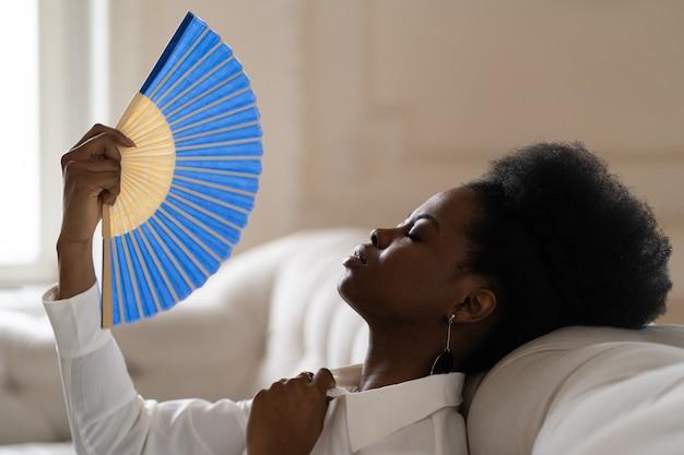 Czarna kobieta biznesu cierpiąca na udar cieplny, siedząca w salonie w domu, korzystająca z machającego wentylatora