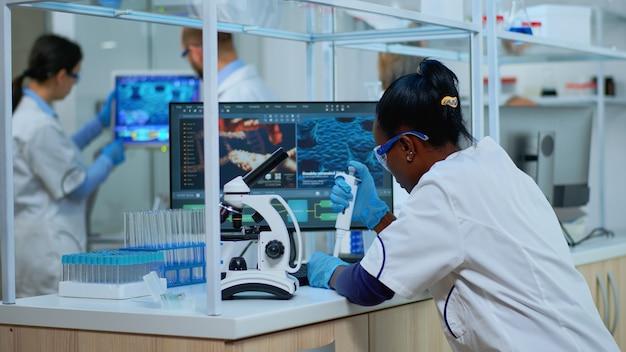 Czarna kobieta chemik analizując reakcję wirusa pod mikroskopem w laboratorium. wieloetniczny zespół badający ewolucję szczepionek przy użyciu zaawansowanych technologii do badań naukowych, opracowania leczenia przeciw covid19