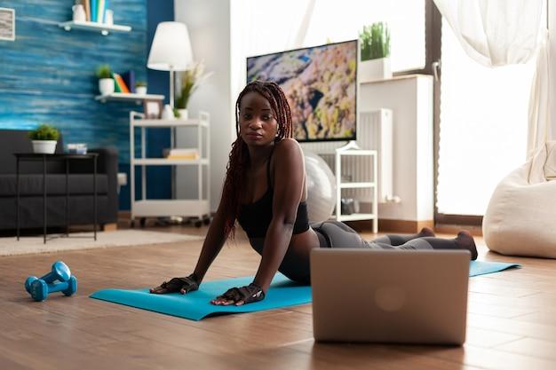 Czarna kobieta ćwiczy i rozciąga swoje ciało