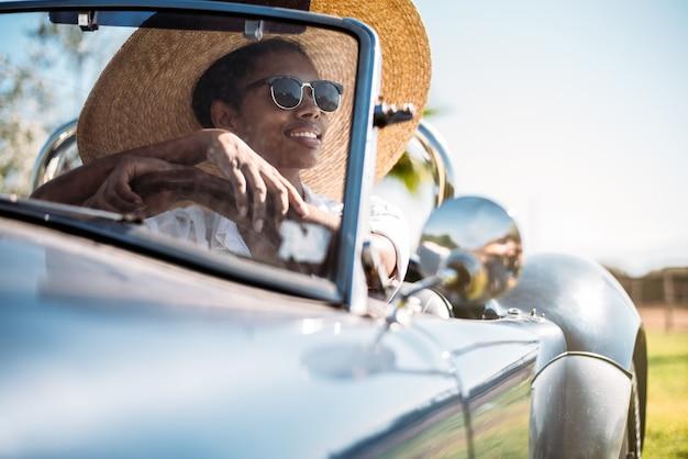 Czarna kobieta jedzie rocznika kabrioletu samochód