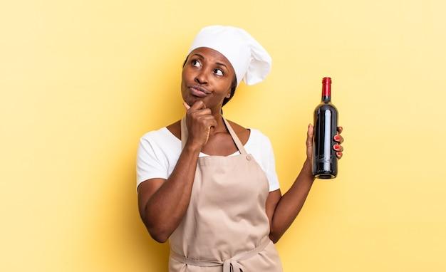 Czarna kobieta kucharz afro myśli, czuje się zwątpienie i zdezorientowana, z różnymi opcjami, zastanawiając się, którą decyzję podjąć. koncepcja butelki wina