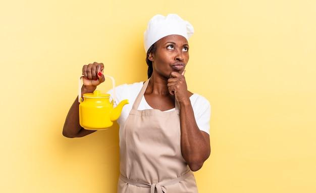 Czarna kobieta kucharz afro myśli, czuje się zwątpienie i zdezorientowana, z różnymi opcjami, zastanawiając się, którą decyzję podjąć. koncepcja czajnika