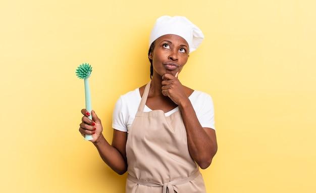 Czarna kobieta kucharz afro myśli, czuje się zwątpienie i zdezorientowana, z różnymi opcjami, zastanawiając się, którą decyzję podjąć. koncepcja czyszczenia naczyń