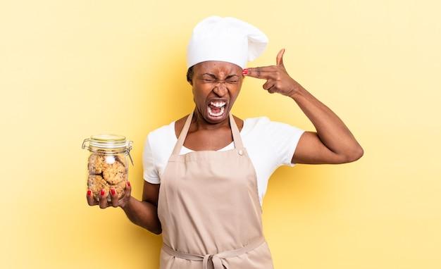 Czarna kobieta kucharz afro patrząc niezadowolony i zestresowany, gest samobójczy, co pistolet znak ręką, wskazując na głowę. koncepcja ciasteczek