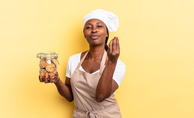 Czarna kobieta kucharz afro robi gest capice lub pieniądze, mówiąc, aby spłacić swoje długi!. koncepcja ciasteczek