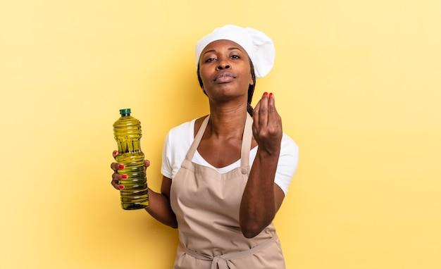Czarna kobieta kucharz afro robi gest capice lub pieniądze, mówiąc, aby spłacić swoje długi!. koncepcja oliwy z oliwek