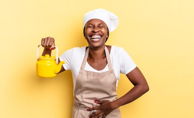 Czarna kobieta kucharz afro śmiejąca się głośno z jakiegoś zabawnego żartu, szczęśliwa i wesoła, dobrze się bawi. koncepcja czajnika
