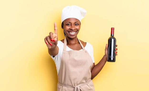 Czarna kobieta kucharz afro uśmiecha się dumnie i pewnie, triumfalnie tworząc pozę numer jeden, czując się jak lider. koncepcja butelki wina