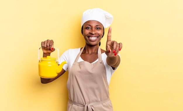Czarna kobieta kucharz afro uśmiecha się dumnie i pewnie, triumfalnie tworząc pozę numer jeden, czując się jak lider. koncepcja czajnika