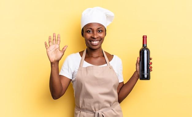 Czarna kobieta kucharz afro uśmiecha się i wygląda przyjaźnie, pokazując numer pięć lub piąty z ręką do przodu, odliczając. koncepcja butelki wina
