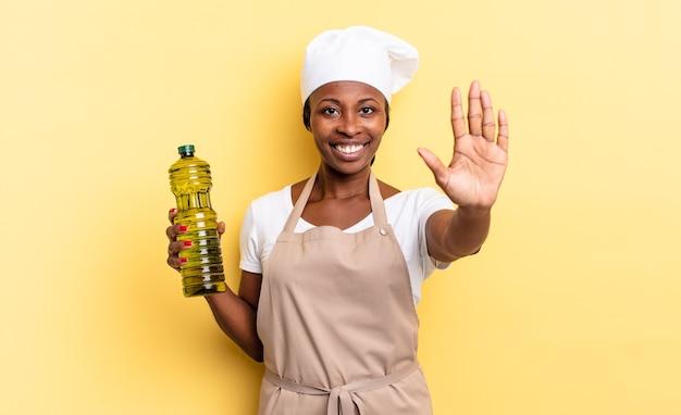 Czarna kobieta kucharz afro uśmiecha się i wygląda przyjaźnie, pokazując numer pięć lub piąty z ręką do przodu, odliczając. koncepcja oliwy z oliwek