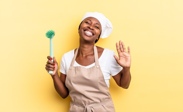 Czarna kobieta kucharz afro uśmiechnięta radośnie i radośnie, machająca ręką, witająca i witająca cię lub żegnająca się. koncepcja czyszczenia naczyń