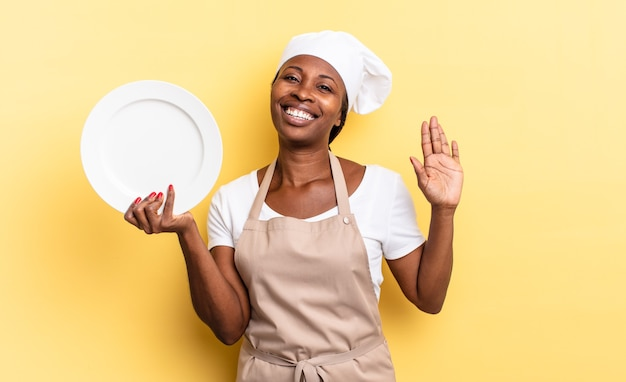 Czarna kobieta kucharz afro uśmiechnięta radośnie i radośnie, machająca ręką, witająca i witająca cię lub żegnająca się. koncepcja pustego talerza