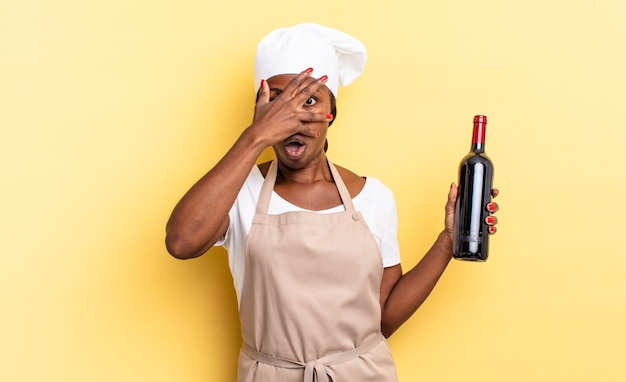 Czarna kobieta kucharz afro wygląda na zszokowaną, przestraszoną lub przerażoną, zakrywając twarz dłonią i zerkając między palcami. koncepcja butelki wina