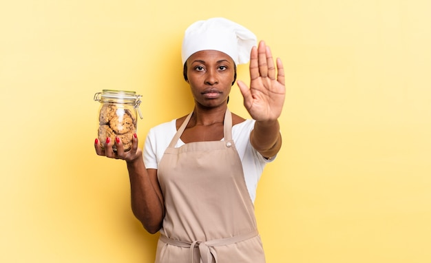 Czarna kobieta kucharz afro wygląda poważnie, surowo, niezadowolona i zła, pokazując otwartą dłoń, robiąc gest zatrzymania. koncepcja ciasteczek