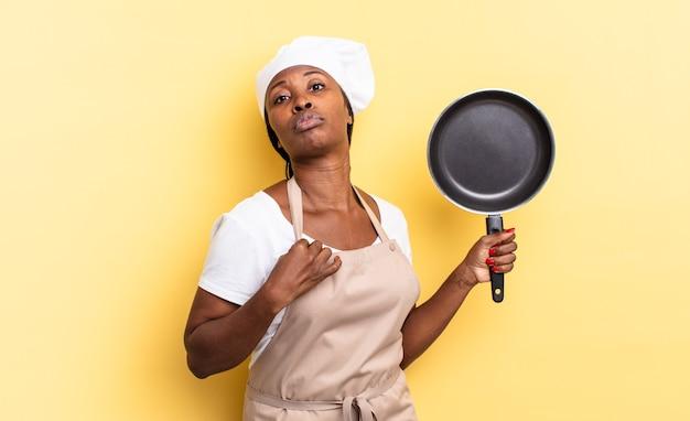 Czarna kobieta kucharz afro wyglądająca arogancko, odnosząca sukcesy, pozytywna i dumna, wskazująca na siebie