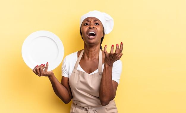 Czarna kobieta kucharz afro wyglądająca na zdesperowaną i sfrustrowaną, zestresowaną, nieszczęśliwą i zirytowaną, krzyczącą i krzyczącą. koncepcja pustego talerza
