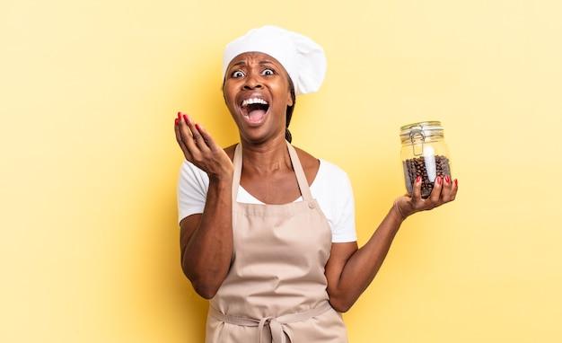 Czarna kobieta kucharz afro wyglądająca na zdesperowaną i sfrustrowaną, zestresowaną, nieszczęśliwą i zirytowaną, krzyczącą i krzyczącą. koncepcja ziaren kawy
