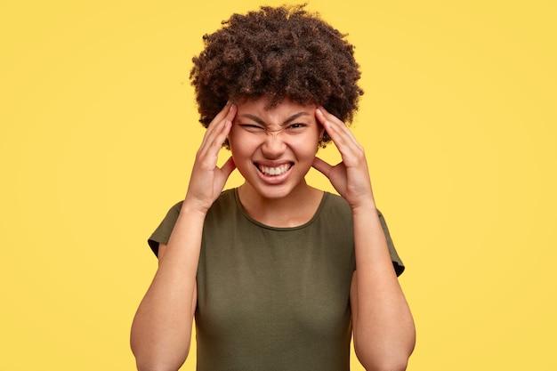 Czarna kobieta marszczy brwi z niezadowoleniem, zaciska zęby, trzyma ręce na skroniach