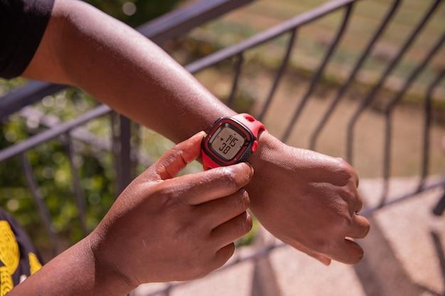 Czarna kobieta mierzy czas jej biegania za pomocą swojego zegarka sportowego