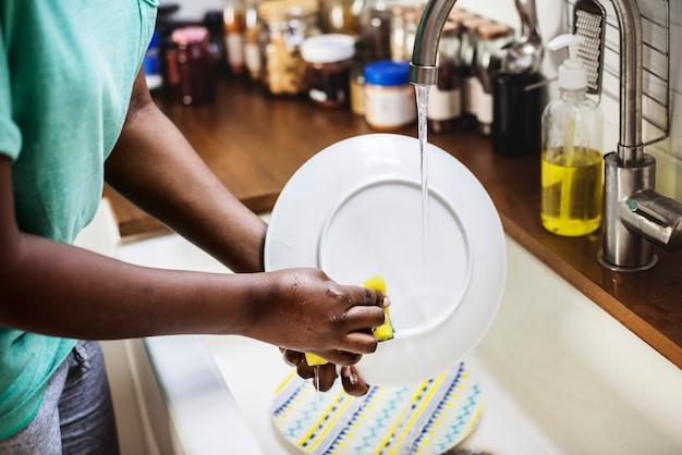 Czarna kobieta myje naczynie