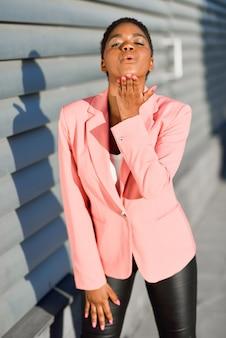 Czarna kobieta o bardzo krótkich włosach całująca.