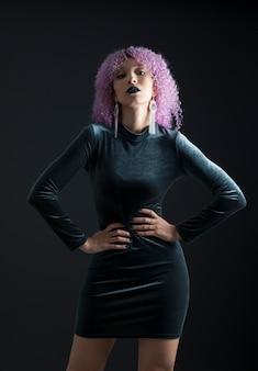 Czarna kobieta o kocim wyglądzie, ubrana w czarną elegancką sukienkę