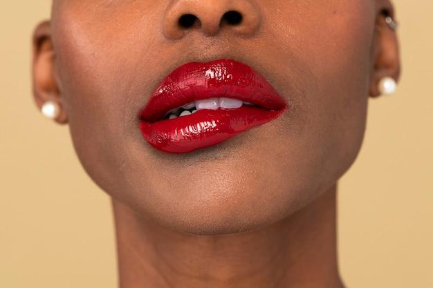 Czarna kobieta przygryzająca czerwone usta