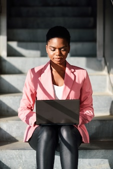 Czarna kobieta siedzi na miejskich schodach pracy z komputerem.