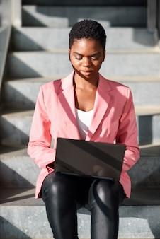 Czarna kobieta siedzi na miejskich schodach pracy z komputerem