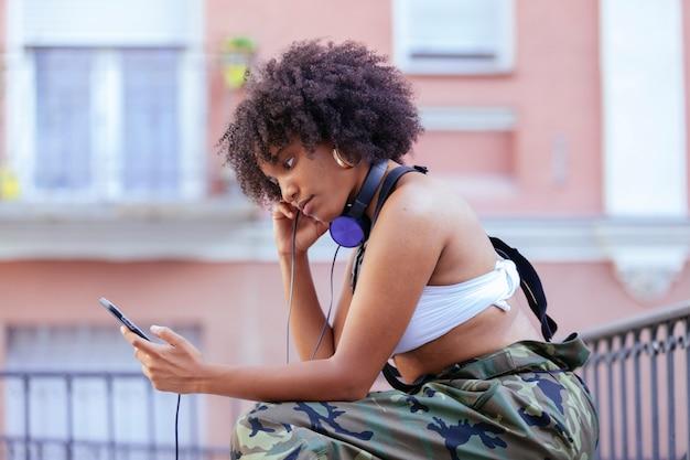 Czarna kobieta słucha fajnej muzyki w słuchawkach