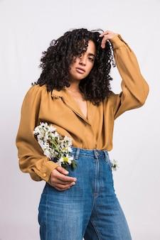 Czarna kobieta stoi z stokrotka kwiaty w kieszeni jeansów