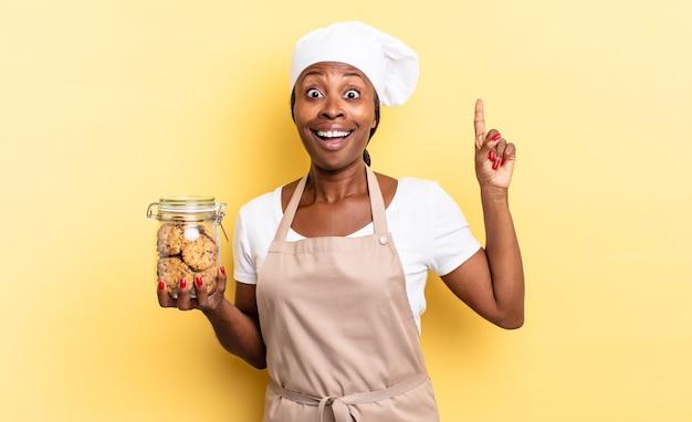 Czarna kobieta szefa kuchni afro czuje się jak szczęśliwy i podekscytowany geniusz po zrealizowaniu pomysłu, radośnie unosząc palec, eureka!. koncepcja ciasteczek