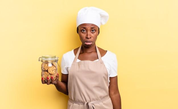Czarna kobieta szefa kuchni afro czuje się smutna i marudna z nieszczęśliwym spojrzeniem, płacze z negatywnym i sfrustrowanym nastawieniem. koncepcja ciasteczek