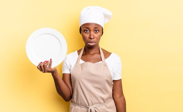 Czarna kobieta szefa kuchni afro czuje się smutna i marudna z nieszczęśliwym spojrzeniem, płacze z negatywnym i sfrustrowanym nastawieniem. koncepcja pustego talerza